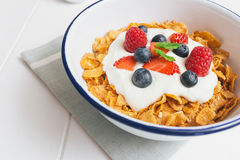 Healthy breakfast with cereals and berries in an e. Top view of healthy breakfast with cerelas, berries, honey and nuts in an enamel bowl on a white wood royalty free stock images