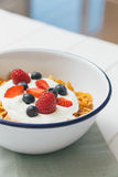 Healthy breakfast with cereals and berries in an e. Top view of healthy breakfast with cerelas, berries, honey and nuts in an enamel bowl on a white wood Stock Photo
