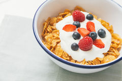 Healthy breakfast with cereals and berries in an e. Top view of healthy breakfast with cerelas, berries, honey and nuts in an enamel bowl on a white wood Royalty Free Stock Image