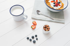 Healthy breakfast with cereals and berries in an e. Top view of healthy breakfast with cerelas, berries, honey and nuts in an enamel bowl on a white wood royalty free stock photos