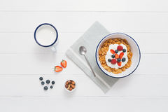 Healthy breakfast with cereals and berries in an enamel bowl. Top view of healthy breakfast with cereals, berries, honey and nuts in an enamel bowl on a white Stock Photography