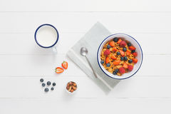 Healthy breakfast with cereals and berries in an enamel bowl. Top view of healthy breakfast with cereals, berries, honey and nuts in an enamel bowl on a white Stock Images