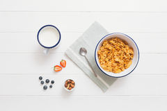 Healthy breakfast with cereals and berries in an enamel bowl. Top view of healthy breakfast with cereals, berries, honey and nuts in an enamel bowl on a white Stock Photo