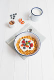 Healthy breakfast with cereals and berries in an enamel bowl. Top view of healthy breakfast with cereals, berries, honey and nuts in an enamel bowl on a white royalty free stock photos