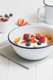 Healthy breakfast with cereals and berries in an enamel bowl. Top view of healthy breakfast with cereals, berries, honey and nuts in an enamel bowl on a white Stock Image