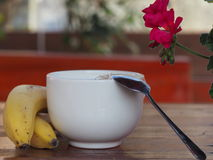 Healthy breakfast with cereals, dairy and bananas. Bananas and cereals bowl on wooden table Royalty Free Stock Images
