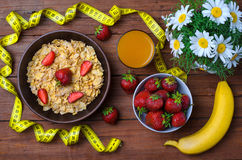 Healthy breakfast: cereals, strawberries, banana and a glass of. Juice. Measuring tape and dietary products on a wooden table, top view Royalty Free Stock Images