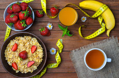 Healthy breakfast: cereals, strawberries, banana and a glass of. Juice. Measuring tape and dietary products on a wooden table, top view Royalty Free Stock Photo