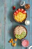 A healthy breakfast of cereals with strawberries and kiwi on a rustic blue background. Muesli and corn flakes, milk, almonds, berr. Y mousse, physalis. Copy Stock Photo