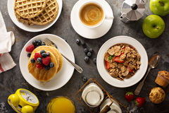 Healthy breakfast with cereals and waffles. Healthy breakfast on the table with cereals, fruit, pancakes and waffles overhead shot Stock Photos