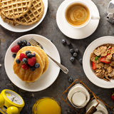 Healthy breakfast with cereals and waffles. Healthy breakfast on the table with cereals, fruit, pancakes and waffles overhead shot Royalty Free Stock Photo