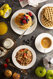 Healthy breakfast with cereals and waffles. Healthy breakfast on the table with cereals, fruit, pancakes and waffles overhead shot Royalty Free Stock Images