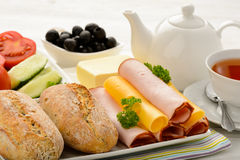 Healthy breakfast with cheese, ham, fresh bun, fresh vegetables, olives and tea. Royalty Free Stock Photo