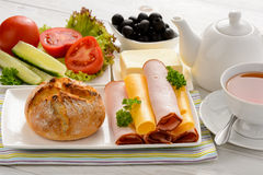 Healthy breakfast with cheese, ham, fresh bun, fresh vegetables, olives and tea. Royalty Free Stock Images
