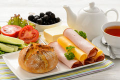 Healthy breakfast with cheese, ham, fresh bun, fresh vegetables, olives and tea. Stock Photography