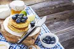 Healthy breakfast classic. Several domestic hot pancakes with fresh ripe blueberry lime zest, honey Stock Image