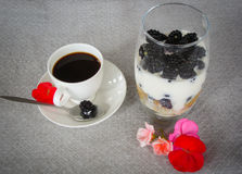 Healthy breakfast coffee and blackberries with yogurt. Healthy breakfast black coffee in a white cup, teaspoon with a berry on a white saucer and blackberries Stock Images