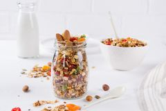 Healthy breakfast concept. Baked granola in white ceramic bowl and glass jar. On the kitchen table royalty free stock photos