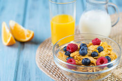 Healthy breakfast concept - cereals with berries, orange juice, orange slices and milk Stock Images