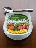 Spinach avocado smothie bowl with fruits and nuts on top stock image