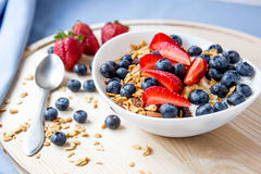Healthy breakfast concept. Granola with blueberries and strawberries in the white bowl. Royalty Free Stock Photo