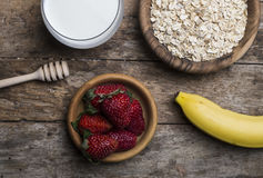 Healthy breakfast concept with oat flakes and fresh berries on rustic background. Royalty Free Stock Photos