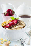 Healthy breakfast. Corn flakes, banana, strawberry, almond, chocolate and yoghurt in a ceramic bowl Royalty Free Stock Photo