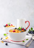 Healthy breakfast with corn flakes and berries. Healthy breakfast with corn flakes, berries and milk on light gray background. Copy space Stock Photo