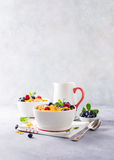 Healthy breakfast with corn flakes and berries. Healthy breakfast with corn flakes, berries and milk on light gray background. Copy space Royalty Free Stock Images