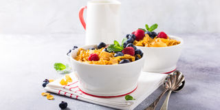 Healthy breakfast with corn flakes and berries. Healthy breakfast with corn flakes, berries and milk on light gray background. Copy space Royalty Free Stock Photos