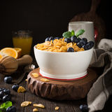 Healthy breakfast with corn flakes and berries. Healthy breakfast with corn flakes, berries and milk on old dark wooden background. Copy space Stock Photography