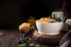 Healthy breakfast with corn flakes and berries. Healthy breakfast with corn flakes, berries and milk on old dark wooden background. Copy space Royalty Free Stock Images