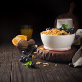Healthy breakfast with corn flakes and berries. Healthy breakfast with corn flakes, berries and milk on old dark wooden background. Copy space Royalty Free Stock Photo