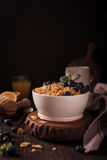 Healthy breakfast with corn flakes and berries. Healthy breakfast with corn flakes, berries and milk on old dark wooden background. Copy space. Retro style toned Royalty Free Stock Image