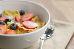Healthy breakfast with corn flakes and berries in white bowl. Shallow focus Royalty Free Stock Images