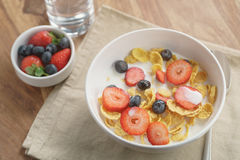 Healthy breakfast with corn flakes and berries in white bowl. Slightly toned photo Stock Image