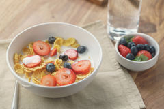 Healthy breakfast with corn flakes and berries in white bowl. Slightly toned photo Royalty Free Stock Photo