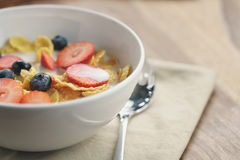 Healthy breakfast with corn flakes and berries in white bowl. Slightly toned photo Stock Images