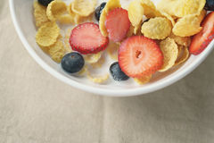 Healthy breakfast with corn flakes and berries in white bowl. Slightly toned photo Royalty Free Stock Photography