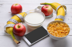 Healthy breakfast: corn flakes and fresh fruit on wooden. Healthy breakfast: corn flakes and fresh fruit on a wooden table. Measuring tape and a telephone, diet Royalty Free Stock Photo