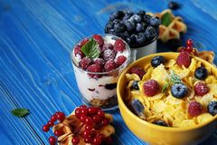 Healthy breakfast. Corn flakes with raspberries and blueberries,. Granola with yogurt and berries, wafers and milk. A great start to the day. Top view. Close up Royalty Free Stock Photo
