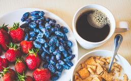 Healthy breakfast. Corn flakes with ripe red strawberry, blue ho. Neysuckle berries and cup of coffee. Selective focus, toned Stock Photo