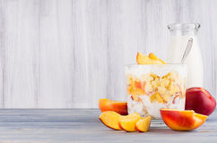 Healthy breakfast with corn flakes, slice peach and milk bottle on white wood board. Decorative border with copy space Royalty Free Stock Images