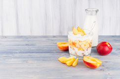 Healthy breakfast with corn flakes, slice peach and milk bottle on white wood board. Decorative border with copy space. Healthy breakfast with corn flakes Royalty Free Stock Photo