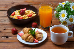 Healthy breakfast: corn flakes, strawberries, tea and croissant. Royalty Free Stock Photos