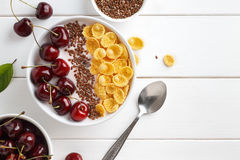 Healthy breakfast with corn flakes, sweet cherry, greek yogurt and flax seeds on white wooden table. Top view with copy space Royalty Free Stock Photos