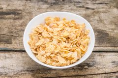 Healthy breakfast . Corn flakes in white bowl on wooden table Royalty Free Stock Photography