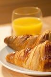 Healthy Breakfast Croissant and Orange Juice. A healthy continental breakfast of croissant pastries, orange juice, Illuminated with golden early morning sunshine Royalty Free Stock Photography