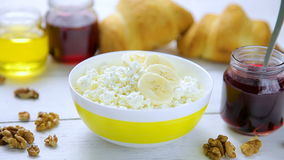 Healthy breakfast - crumbly, cottage cheese with banana, walnuts, croissants, honey and lingonberry jam in a bowl stock footage