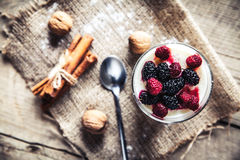 Healthy breakfast - Dairy yogurt with raspberry, mulberry on wooden background Royalty Free Stock Images